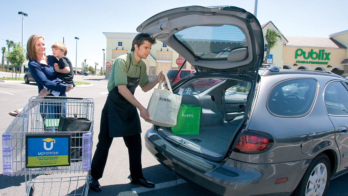 A Publix bagger helps a customer load groceries